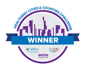 Healthiest Cities & Counties Challenge WINNER, cityscape, APHA, Aetna Foundation, NaCo logos